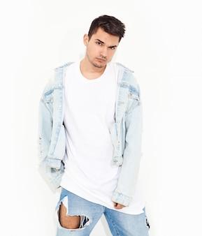 ポーズジーンズ服に身を包んだハンサムな若いモデルの男の肖像画。孤立した