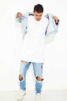 Портрет красивого молодого модельного человека одел в представлять одежд джинсов. изолированные