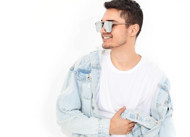 Портрет красивый улыбающийся молодой модельный человек, одетый в джинсовой одежде в солнцезащитные очки позирует. изолированные