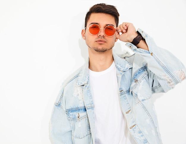 Портрет красивого молодого модельного человека одел в джинсовой одежде в изложении солнцезащитных очков. изолированные