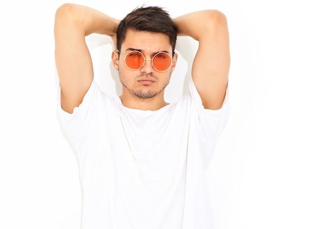 Портрет красивого молодого модельного человека одел в джинсовой одежде и футболке в изложении солнцезащитных очков. касаясь его голове