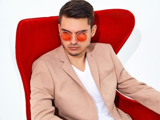 赤い椅子に座ってエレガントな明るいピンクのスーツに身を包んだハンサムなファッションスタイリッシュなビジネスマンモデルの肖像画。メトロセクシャル