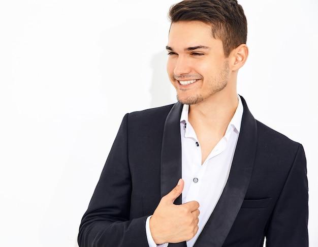 エレガントな黒の古典的なスーツポーズに身を包んだハンサムな笑顔スタイリッシュなビジネスマンモデルの肖像画。メトロセクシャル