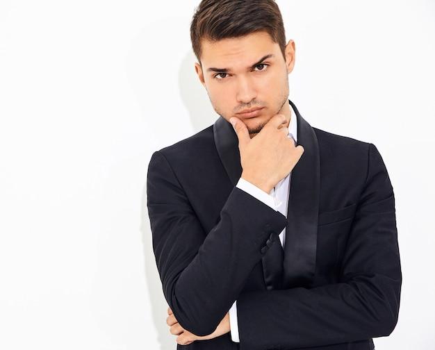 エレガントな黒の古典的なスーツに身を包んだハンサムなファッションスタイリッシュなビジネスマンモデルの肖像画。彼のあごに触れる