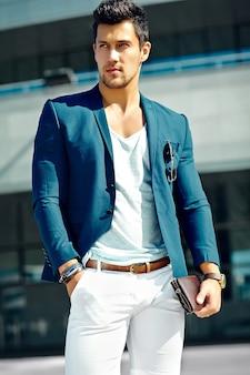 ファッション性の高い外観。通りで青いスーツ布ライフスタイルで若いスタイリッシュな自信を持って幸せなハンサムな実業家モデル男