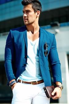 通りの背景にポーズをとってエレガントなスーツに身を包んだセクシーなハンサムなファッション男性モデル男の肖像