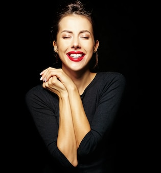 Портрет веселой улыбающейся модной девушки в повседневной черной одежде с красными губами на черном фоне