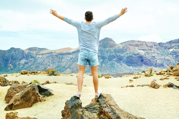 太陽に上げられた手で山の崖の上に立って、成功を祝うカジュアルな流行に敏感な服で幸せなスタイリッシュな男