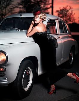 明るい化粧と古い車に座っているレトロなスタイルの巻き毛のヘアスタイルと美しいセクシーなファッションのブロンドの女の子モデル