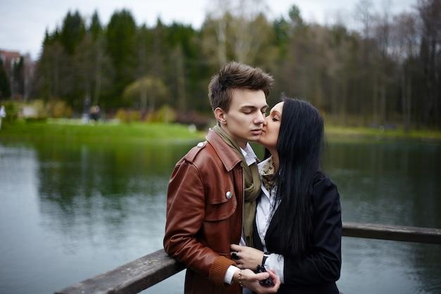公園で立っている美しいロマンチックなファッションカップルの官能的な肖像画。ブルネットの少女