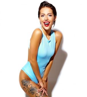 白い背景の上のカジュアルな夏の青い体ランジェリーで美しいホットセクシーなブルネットの女性悪い女の子の肖像画
