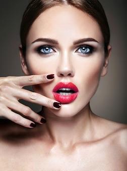 夜の化粧とロマンチックな髪型の美しい少女モデルの肖像画。彼女の赤い唇に触れる