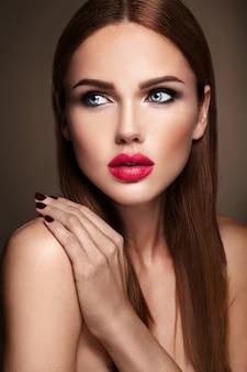 Портрет красивой девушки модели с вечернего макияжа и романтической прически. красные губы