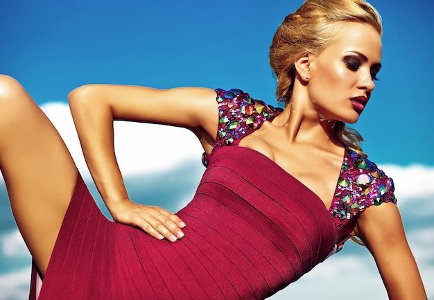 Молодая сексуальная блондинка модель в вечернем красном платье позирует на фоне голубого неба