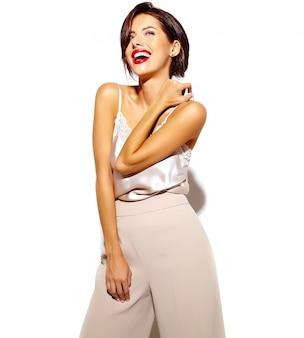 Портрет красивой счастливой милой сексуальной брюнетки с красными губами в широких классических брюках на белом фоне