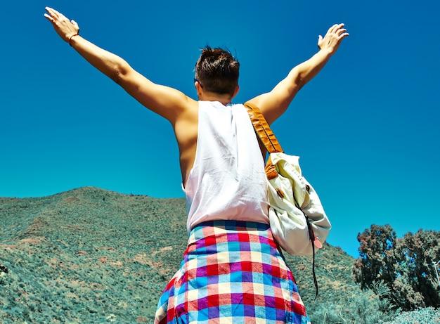 太陽に上げられた手で山の前でジャンプし、成功を祝うカジュアルな流行に敏感な服で幸せなスタイリッシュな男