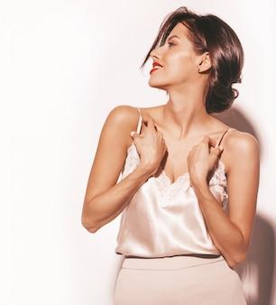 Портрет красивой чувственной брюнетки женщины. девушка в элегантной бежевой классической одежде и широких брюках. модель изолированная на белизне