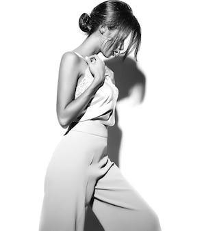 エレガントな白い古典的な服と白い背景のワイドパンツで美しい官能的なブルネットの女性少女の肖像画