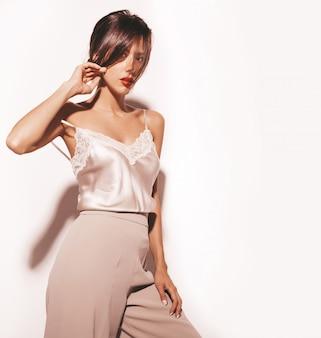 美しい官能的なブルネットの女性の肖像画。エレガントなベージュの古典的な服と広いパンツの女の子。白で隔離モデル