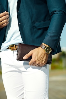 手にアクセサリーとカジュアルな布スーツの青年実業家ハンサムなモデル男のファッションポートレート