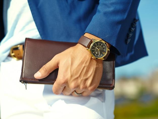 Фасонируйте портрет молодого бизнесмена красивого модельного человека в вскользь костюме ткани с аксессуарами на руках