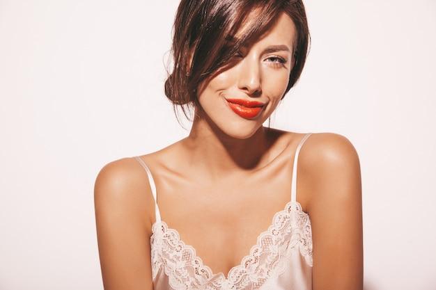 美しい官能的なブルネットの女性の肖像画。エレガントなベージュの古典的な服の女の子。白で隔離される赤い唇とモデル