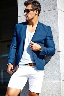 ファッション性の高い外観。サングラスで通りに青いスーツ服の若いスタイリッシュな自信を持って幸せなハンサムな実業家モデル男