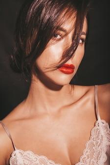 美しい官能的なブルネットの女性のクローズアップの肖像画。エレガントなベージュの古典的な服の女の子。黒に分離された赤い唇とモデル