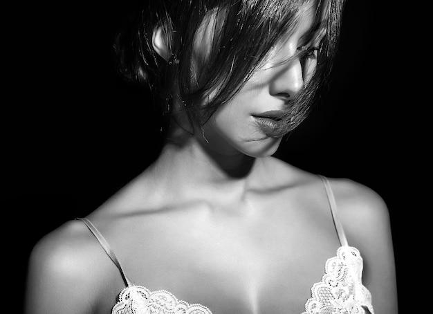 黒の背景にパジャマランジェリーの赤い唇と美しい官能的なかわいいセクシーなブルネットの女性の肖像画。彼女の髪を覆う髪と