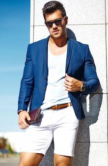 ファッション性の高い外観。空の後ろにサングラスの通りに青いスーツ服の若いスタイリッシュな自信を持って幸せなハンサムな実業家モデル男