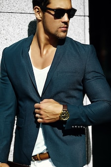 通りにサングラスでカジュアルな布スーツの若いセクシーな実業家ハンサムなモデル男のファッションポートレート