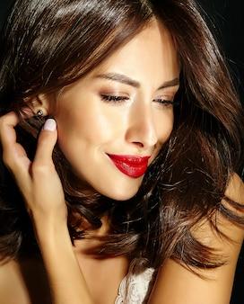Портрет красивой чувственной милой сексуальной брюнетки с красными губами смотрит в коробку настоящего