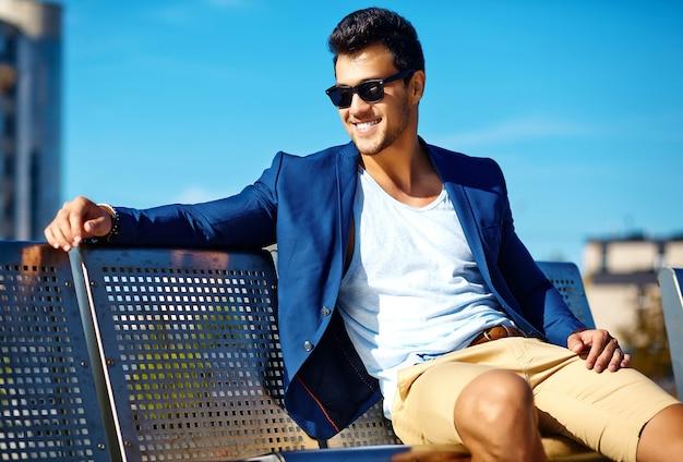 ファッション性の高い外観。ベンチに座って通りに青いスーツ服の若いスタイリッシュな自信を持って幸せなハンサムな実業家モデル男