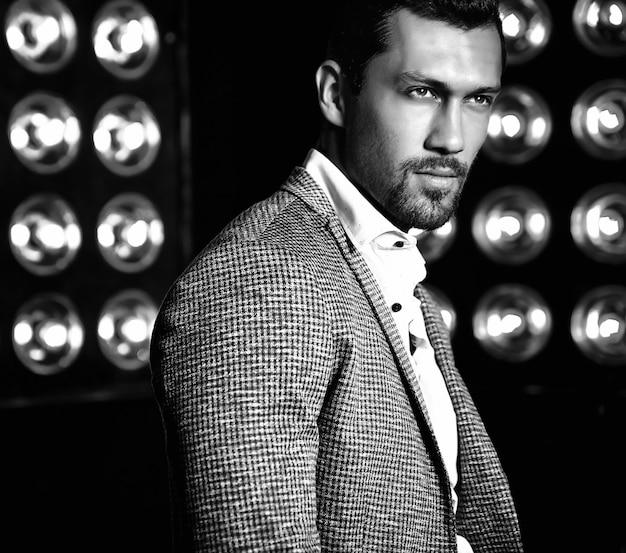 Портрет сексуального красивого модного мужчины модели человека, одетого в элегантный костюм на черном фоне студии огни