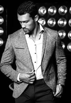 黒のスタジオライトの背景にエレガントなスーツに身を包んだセクシーなハンサムなファッション男性モデル男の肖像
