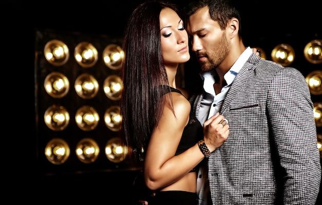 黒のスタジオライトの背景にポーズ美しいセクシーな女性とスーツを着たハンサムなエレガントな男のファッション写真