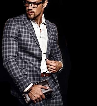 Портрет сексуального красивого модного мужчины модельного человека, одетого в элегантный костюм на черном фоне