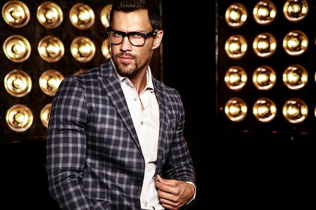 Портрет сексуального красивого модного мужчины модели человека, одетого в элегантный костюм на черном фоне студии огни в очках
