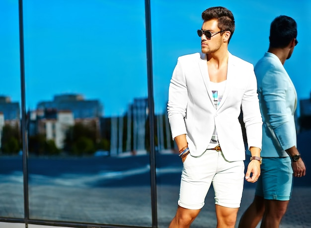 ファッション性の高い外観。若いスタイリッシュな自信を持って幸せなハンサムな実業家モデル男白いスーツ服ポーズと鏡の近くで反射