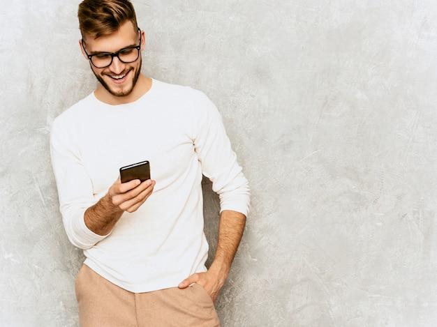 カジュアルな夏の白い服を着てハンサムな笑みを浮かべて流行に敏感なビジネスマンモデルの肖像画。