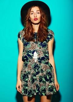 ファッション性の高い外観。帽子の青色の背景に夏の明るい流行に敏感な布で面白いグラマースタイリッシュなセクシーな笑顔の美しい若い女性モデル