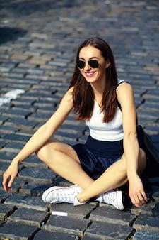 通りに座っている夏の明るい流行に敏感な布で面白いスタイリッシュなセクシーな笑顔の美しい若い女性モデル