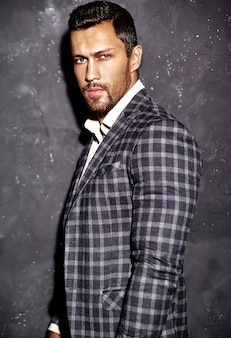 灰色の壁に近いポーズのエレガントなスーツに身を包んだセクシーなハンサムなファッションの男性モデルの男の肖像