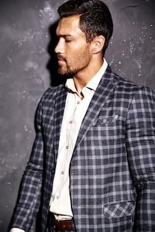 Портрет сексуальный красивый модный мужчина модель мужчина одет в элегантный костюм позирует возле серой стены