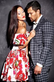 Фасонируйте фото красивого элегантного человека в костюме при красивая сексуальная женщина представляя около серой стены