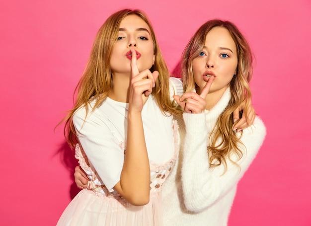 Две молодые красивые улыбающиеся женщины в модных летних белых одеждах