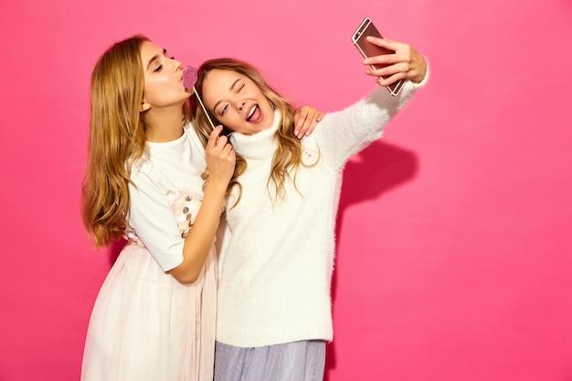Портрет двух молодых стильных улыбающихся белокурых женщин