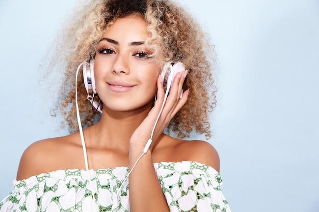 女性の笑みを浮かべて、ヘッドフォンで音楽を聴く
