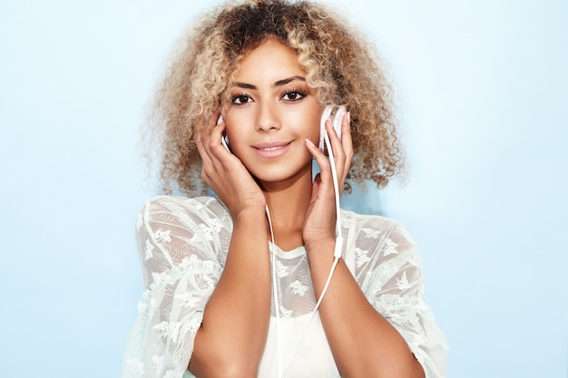 笑みを浮かべて、ヘッドフォンで音楽を聞いて金髪のアフロの髪型と幸せなファッション女性