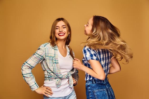 Две молодые красивые блондинки улыбаются в модные летние клетчатые рубашки